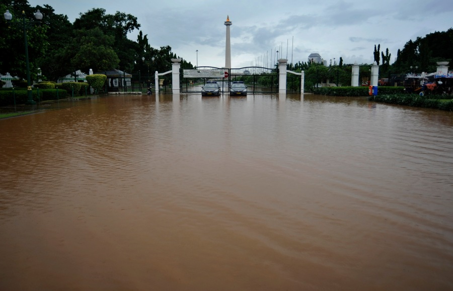 Air hujan membanjiri pintu masuk Monas di seberang Istana Merdeka, Jakarta Pusat, Sabtu (22/12).